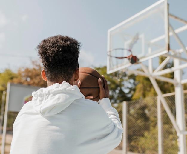 Молодой человек играет в баскетбол на открытом воздухе