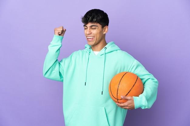 勝利を祝って孤立した紫色の背景の上にバスケットボールをする若い男
