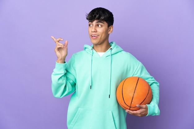 격리 된 보라색 배경 위에 농구를하는 젊은 남자가 손가락을 들어 올리는 동안 솔루션을 실현하려고합니다.