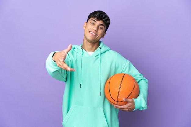 かなり閉じるために孤立した紫色の握手でバスケットボールをしている若い男