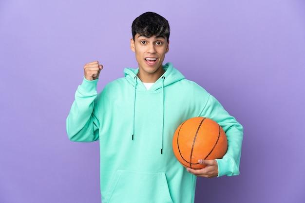 勝者の位置での勝利を祝う孤立した紫色の壁の上でバスケットボールをしている若い男