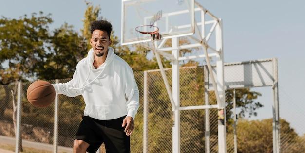コピースペースでバスケットボールをする若い男