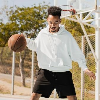 バスケットボールをしている若い男