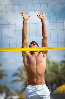 Young man playing beach volleyball on the beach on a sunny day