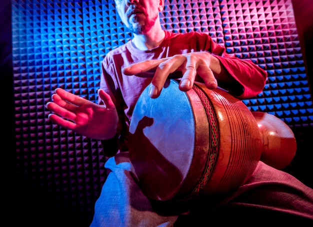Young man playing on djembe in sound recording studio.