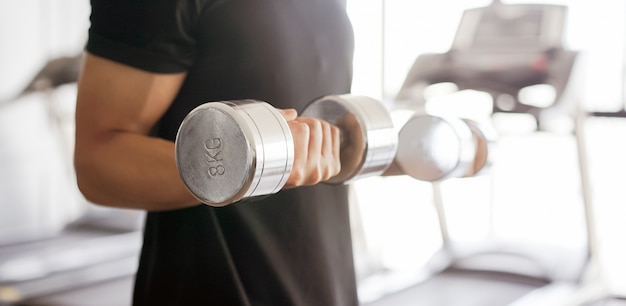 Young man playing dumbbell curl for building bicep muscle at gym