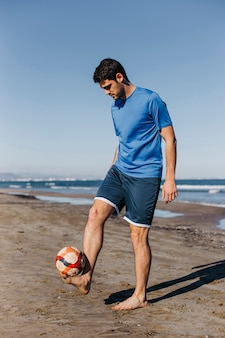 Young man playing football at the beach