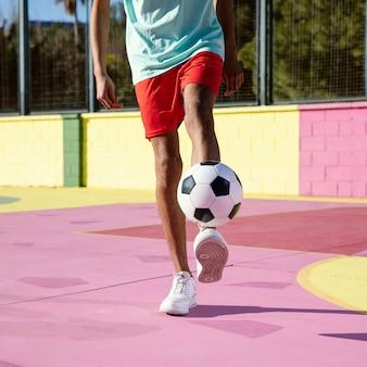 Молодой человек играет в футбол крупным планом