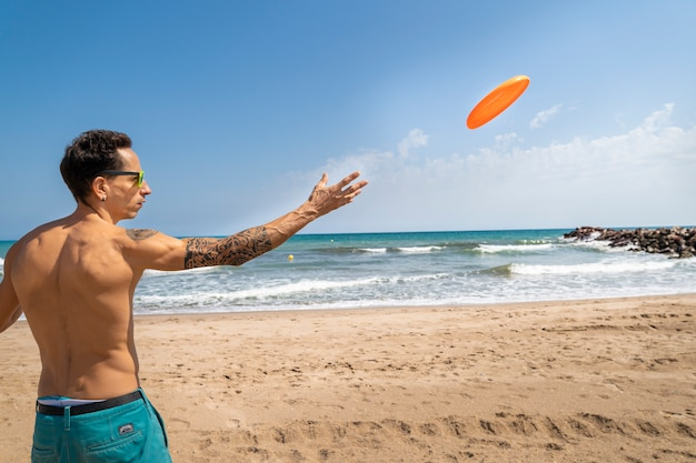 Young man playing the frisbee in the beach