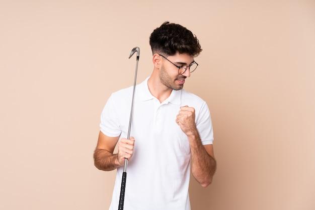Молодой человек играет в гольф и празднует победу