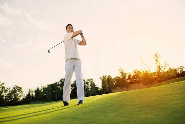 Young man playing golf taking swing shot on a lawn.