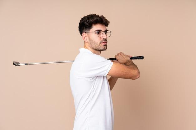 Молодой человек играет в гольф