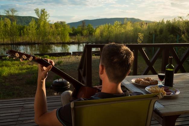 Молодой человек играет на гитаре и пьет вино в одиночку