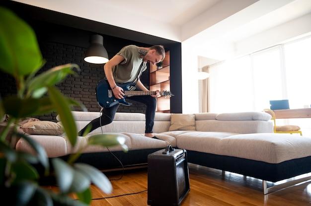 家でギターを弾く若い男