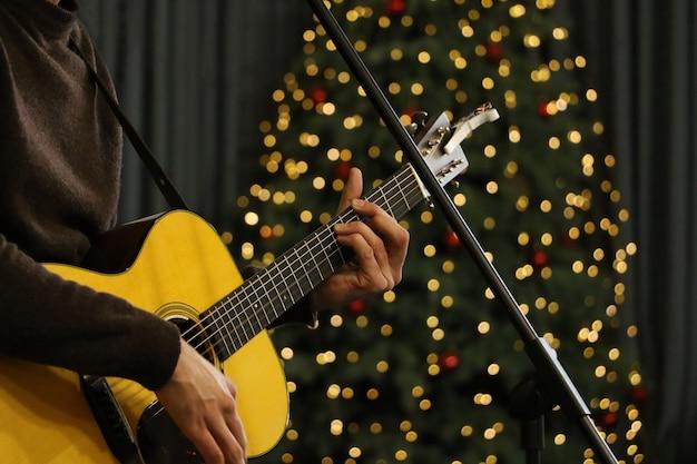 기타를 연주하는 젊은 남자. 주변의 축제 분위기 - 배경에 밝은 보케. 사진을 닫습니다.