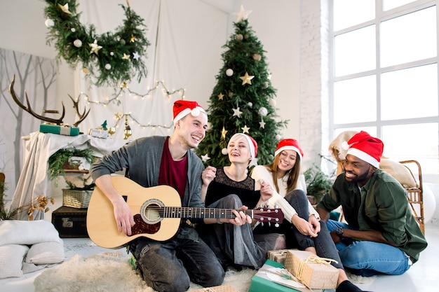 Young man playing guitar and friends are smiling and singing sitting near christmas tree