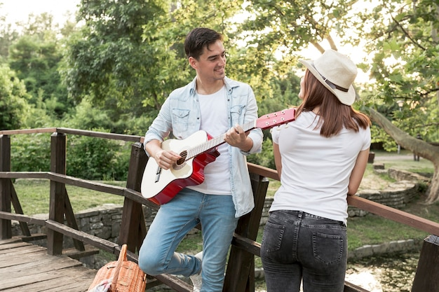 Young man playing the guitar to his girlfriend