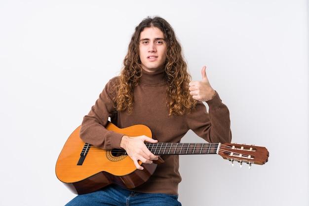 기타를 연주하는 젊은 남자가 웃고 엄지 손가락을 올리는 격리