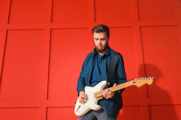 色の表面の近くでギターを弾く若い男