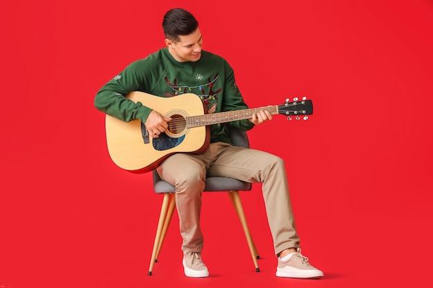 赤でギターを弾く若い男
