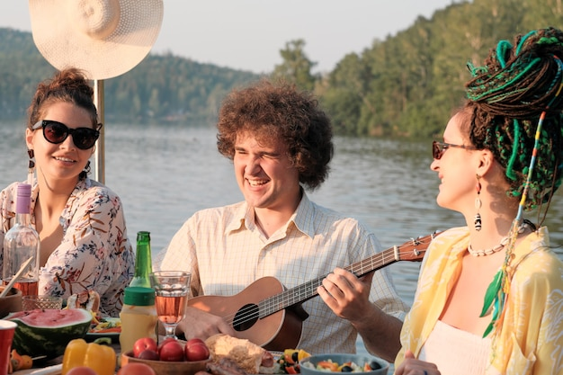 Young man playing guitar with two women sitting between him and singing during their lunch on the nature