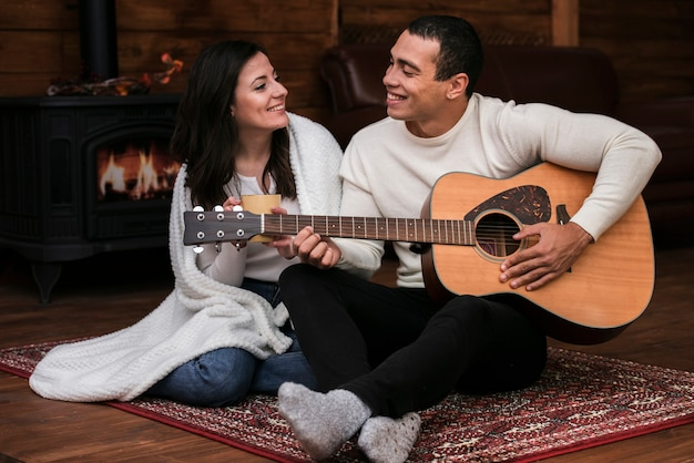 Young man playing guitar to woman