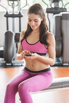 체육관에서 운동하는 동안 휴식을 취하는 동안 이동 전화를 재생하는 젊은 남자