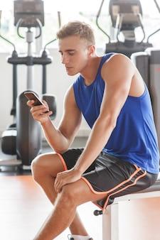 Молодой человек играет в мобильный телефон во время перерыва во время тренировки в тренажерном зале