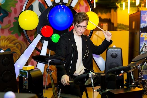 電子ドラムで遊んでいる若い男
