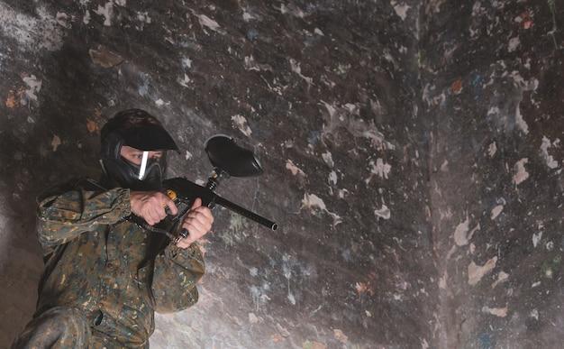 위장과 보호 마스크, 배너, 여가 활동을 착용하고 친구와 함께 페인트 볼 전투 게임을하는 젊은 남자