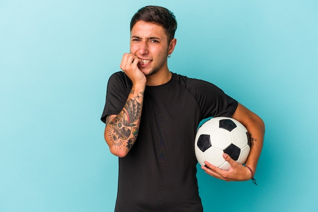 青の背景に孤立したボールを持ってサッカーをしている若い男が指の爪を噛んで、神経質で非常に心配しています。