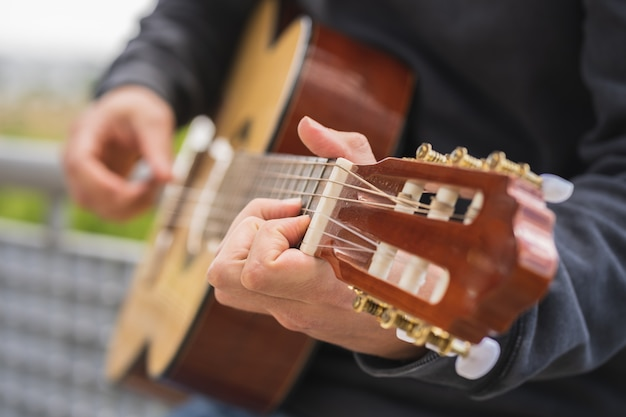 フィールドでスペインのギターを弾く若い男