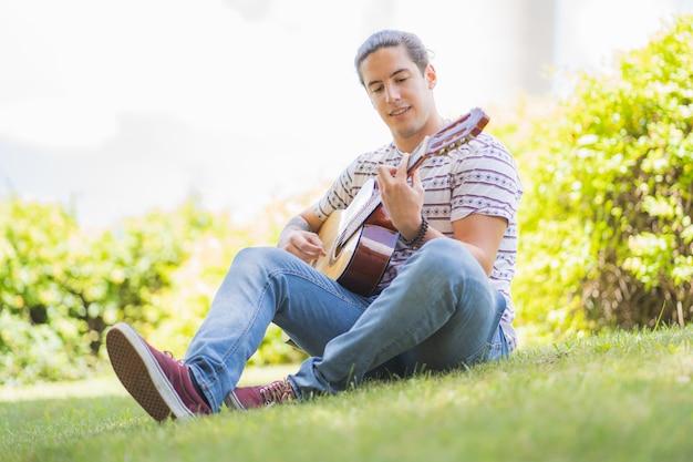 フィールドに笑みを浮かべてスペインのギターを弾く若い男