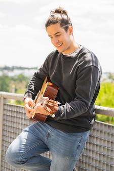 若い男がスペインのギターを弾く