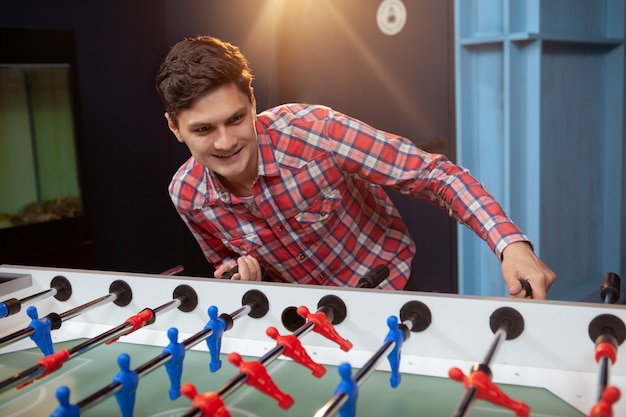 Young man playing table soccer