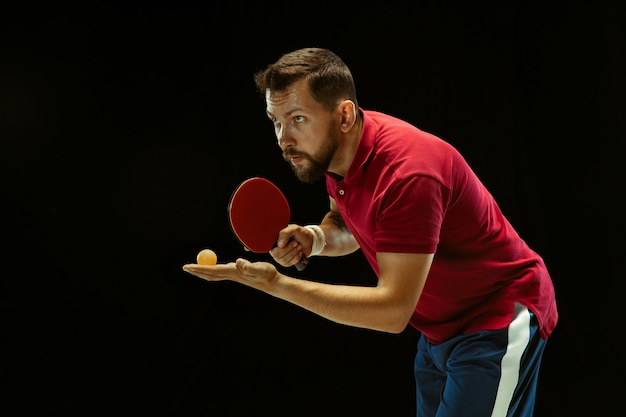 Young man playing table tennis on black studio