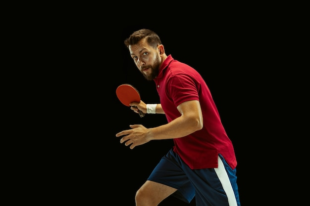 Young man playing table tennis on black