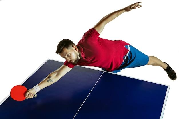 Молодой человек играет в настольный теннис на фоне белой студии Premium Фотографии