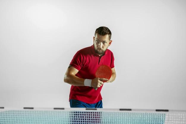 Молодой человек играет в настольный теннис на белой стене студии