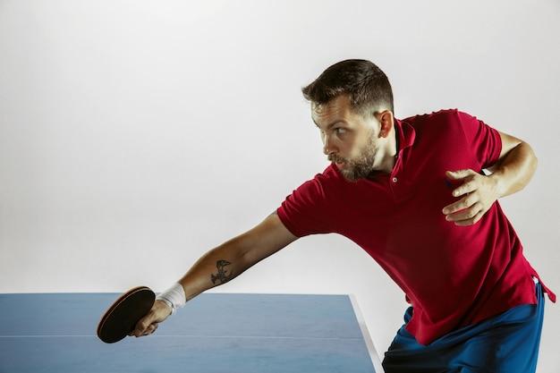 화이트 스튜디오 벽에 탁구를 재생하는 젊은 남자
