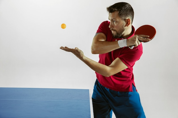 Young man playing table tennis on white  wall