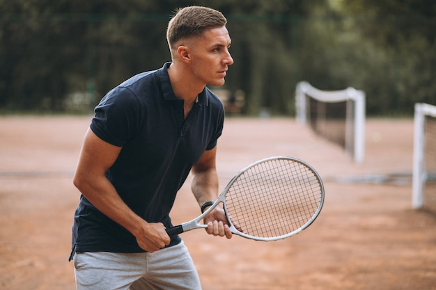 Young man playing tennis at the court