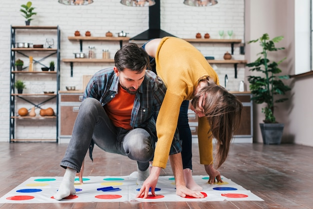Young man playing twister game with her wife at home