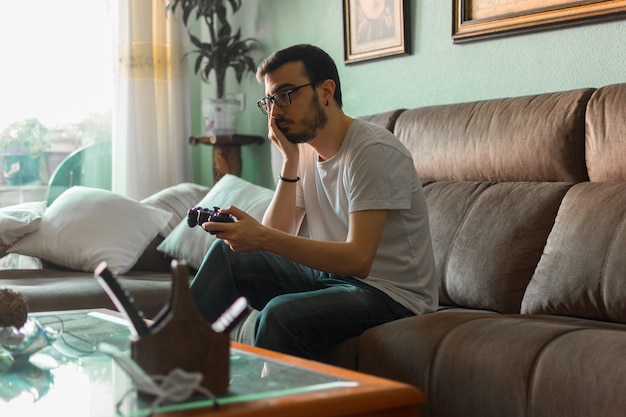 Young man playing video game holding wireless controller