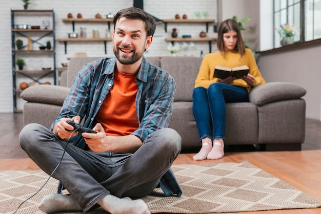 Young man playing the video game with joystick and her wife sitting on sofa at backdrop