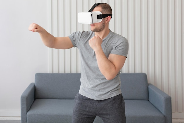 Young man playing videogames while wearing virtual reality goggles