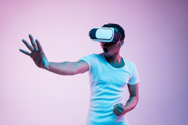 Young man playing in vr-glasses in neon light