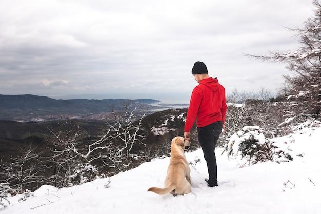 눈 덮인 산에서 그의 개를 노는 젊은 남자