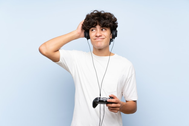 Young man playing with a video game controller over isolated blue wall having doubts and with confuse face expression