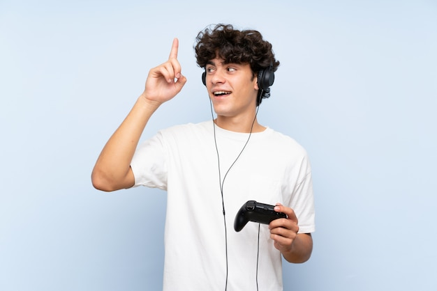 Young man playing with a video game controller over isolated blue wall intending to realizes the solution while lifting a finger up